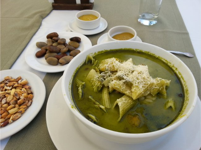 Food in Peru - Green coloured soup with pasta and grated cheese on top
