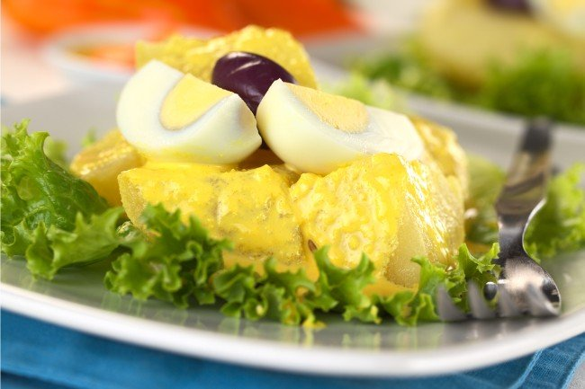 Papa a la Huancaina - What to Eat in Peru - Boiled Potatoes on a bed of lettuce with a yellow sauce topped with a boiled egg and black olive