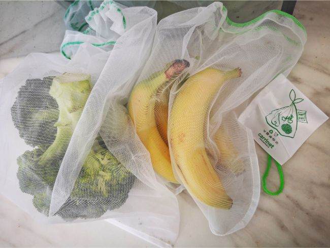 Reusable fruit and veg bags with bananas and broccoli in them