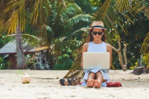 Digital Nomad Lifestyle Tips - How to Get a Healthy Work Life Balance as a Digital Nomad - Woman on beach with laptop