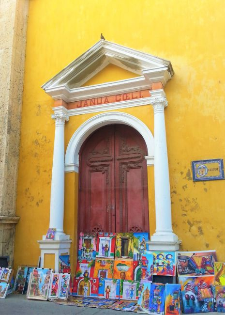 Colourful Cartagena Yellow Church with Arched Doorway and colourful artwork paintings propped up for sale in the doorway- Solo Travel in Colombia