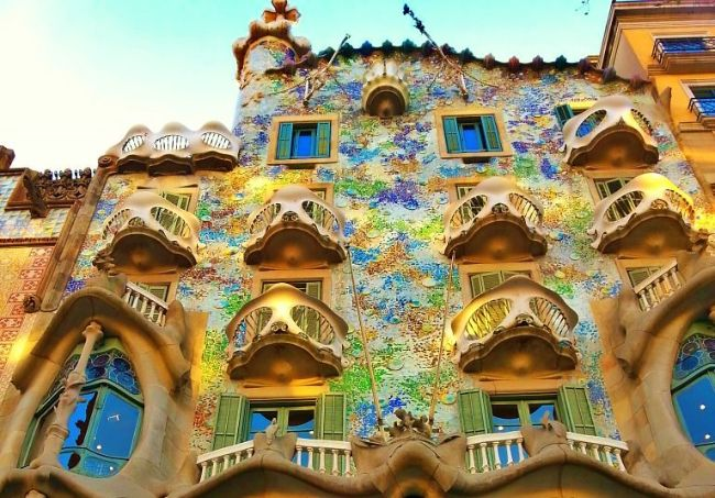 The Facade of Gaudi's Casa Batllo in Barcelona Spain coloured with yellow, blue, green and purple tiles