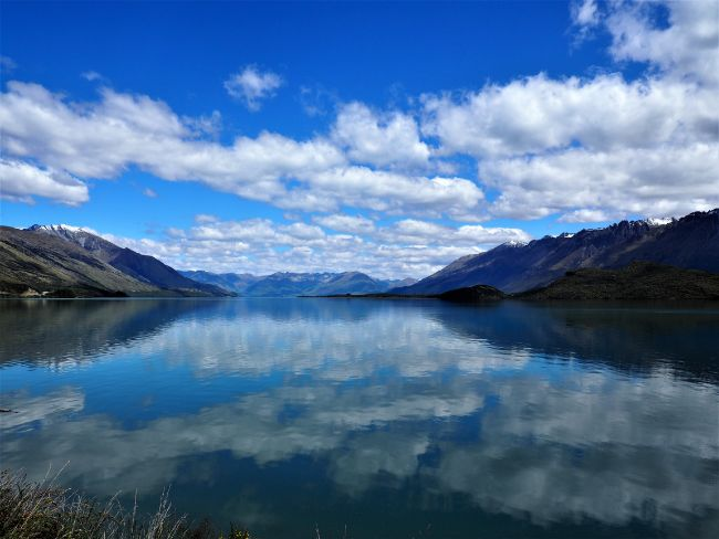Beautiful lake with reflections of the blue sky and clouds in the still water - Lake Wakatipu. Queenstown New Zealand - Safe Places for Solo Female Travel