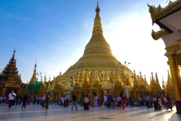 Golden spire temple with a crowd of people in front - Myanmar - The Best Places for Solo Female Travel