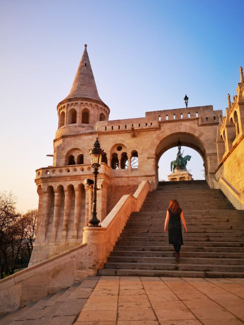 Solo Female Travel in Budapest - Hungary - Claire walking up steps away from camera to a turret and statue in an archway at the top of the steps