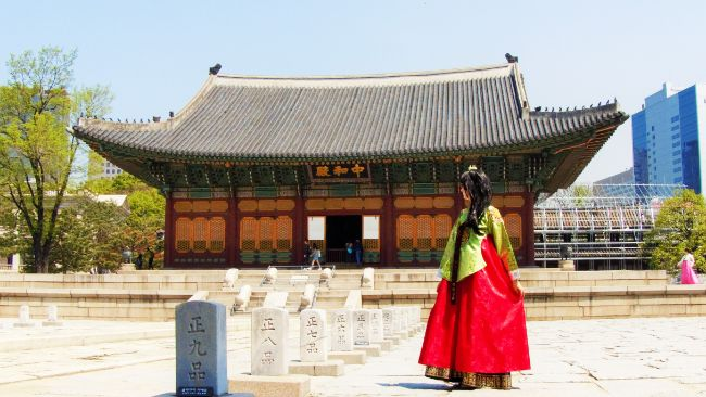 Korean temple and woman in a traditional red dress - Solo Travel in Seoul South Korea