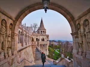 The Best Places for Solo Female Travel Fishermen's Bastion at Sunrise with Claire walking up some steps under an archway with a turret behind her - Budapest