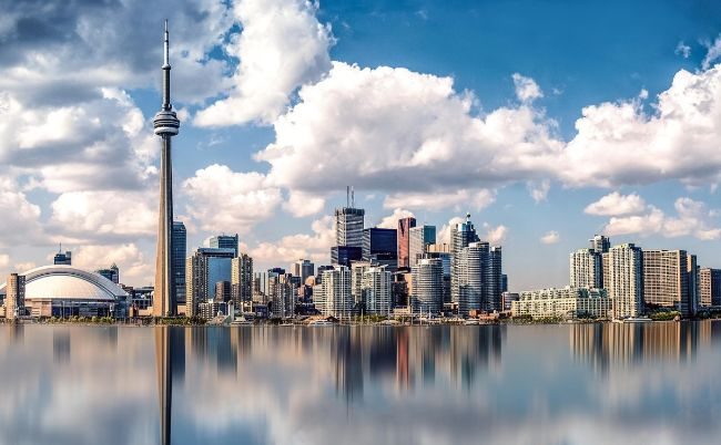 Toronto Skyline from the water with reflections and blue sky with white clouds - The Best Places for Solo Travel