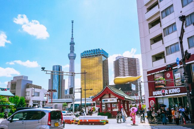 Where to Travel Solo - Modernity Meets Tradition in Tokyo Japan - street view of Tokyo with Sky Tree tower in background, a woman in traditional dress and a Burger King all in same shot