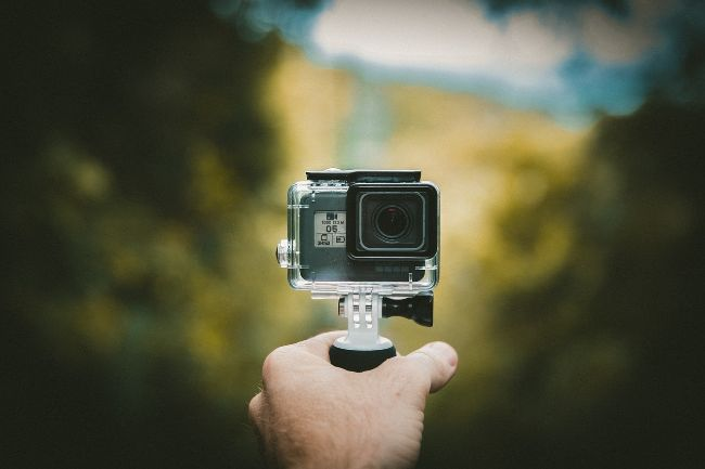 Hand holding A Go Pro action camera - Travel Gifts for Travel Lovers