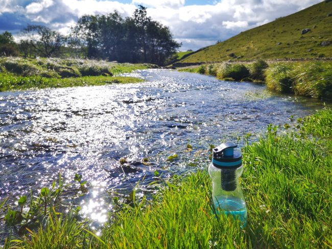 The Water To Go Filter Bottle next to a river in the grass