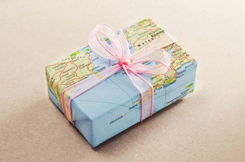 Unique Travel Gifts for Travel Lovers - gift wrapped in a world map tied with a pink bow